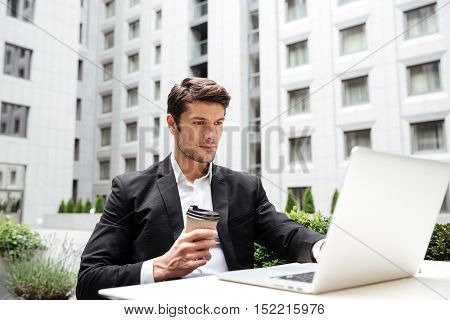 Handsome young businessman working with laptop and drinking coffee outdoors