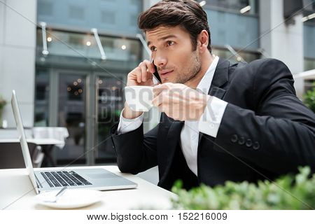 Serious young businessman talking on cell phone and drinking coffee in outdoor cafe