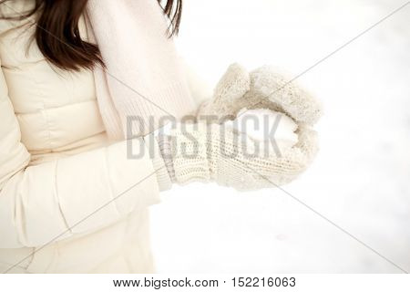people, season, christmas, winter and snow concept - close up of woman with snowball