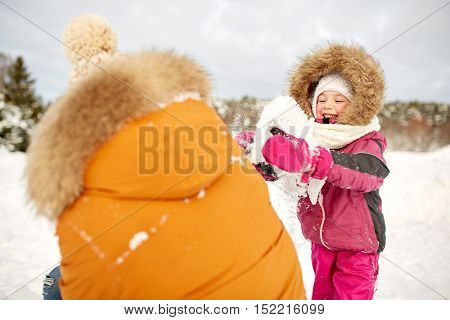 family, parenthood, fatherhood, season and people concept - happy father and little girl in winter clothes playing outdoors with snow