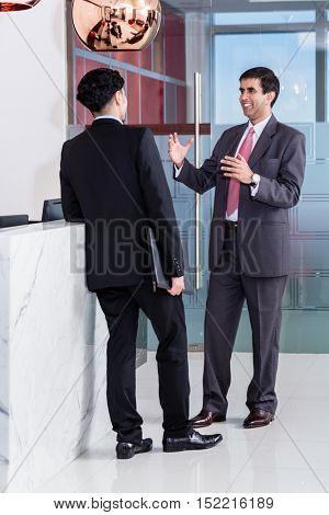Asian executive Manager and affiliate leaning at front desk of office building and talking about business