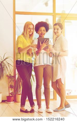 business, technology, people and teamwork concept - happy international creative team of three women with tablet pc computer and coffee in office