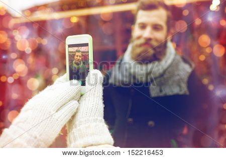 holidays, winter, christmas, technology and people concept - happy couple of tourists in warm clothes taking picture with smartphone in old town