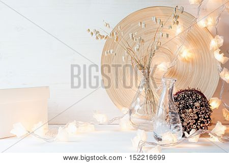 Christmas home decoration with lights on white wooden background. Interior.