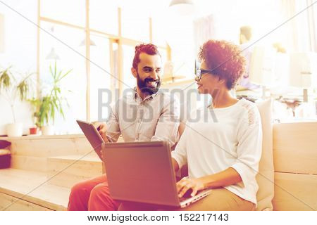 business, startup, technology and people concept - happy international creative team with laptop and tablet pc computer at office