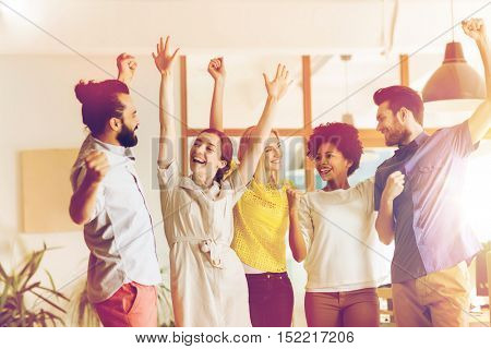 business, triumph, gesture, people and teamwork concept - happy international creative team raising hands up and celebrating victory in office