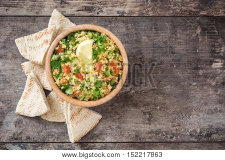 Tabbouleh salad with couscous and pita bread on rustic table