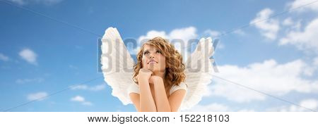people, holidays, christmas and religious concept - happy young woman or teen girl with angel wings over blue sky and clouds background