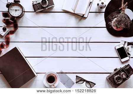 Artistic white background with different vintage and retro things on it, such as retro camera, film, coffee cup, notepad, etc