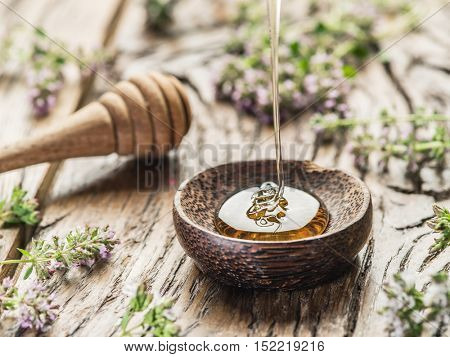 Herbal honey pouring into the wooden bowl. Bowl is on old wooden table surrounded with levender flowers.