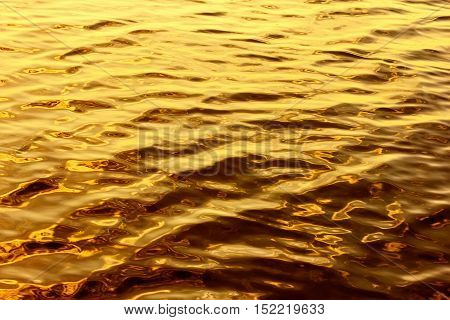 Surface gold-colored liquid, like a the liquid metal