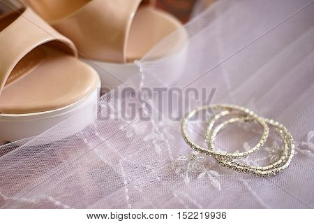 Bride shoes and wedding accessories on a background of a veil.