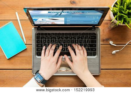 mass media, business, people and technology concept - close up of woman or student typing on laptop computer with world news web page on screen notebook and earphones on wooden table