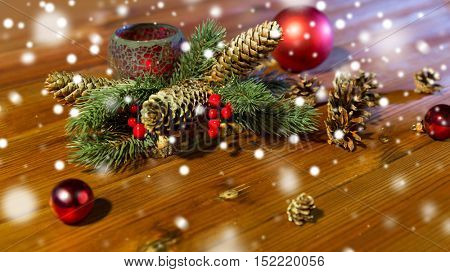 christmas, decoration, holidays and new year concept - close up of natural fir branch decoration with fir-cones, balls and candle in lantern on wooden table