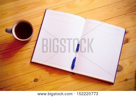 Cup of tea pen opened organizer on wooden background