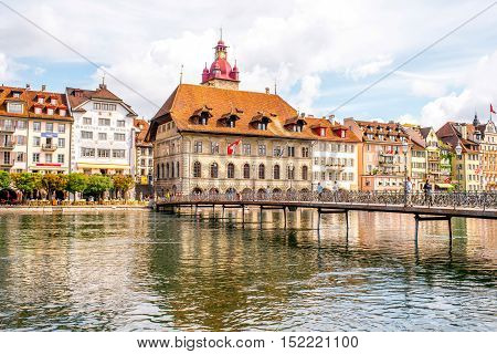 Lucerne, Switzerland - June 27, 2016: View on the riverside with city hall tower and pedestrian bridge in Lucerne old town in Switzerland