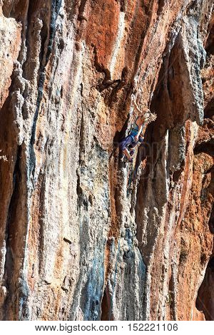 Young cute Female Climber makes difficult Move leading multi pitch route on colorful orange rocky Wall less saturated high contrast Rock