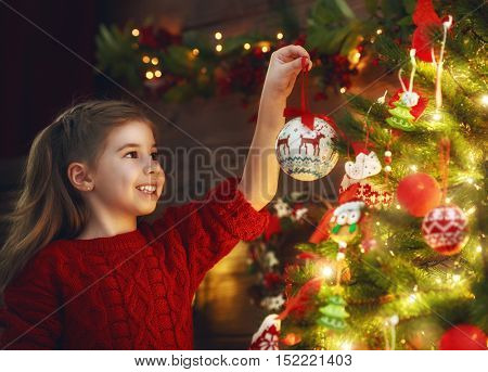 Merry Christmas! Cute little child girl is decorating the Christmas tree.