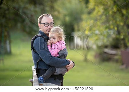 Young father with his daughter in baby carrier outside in green nature.