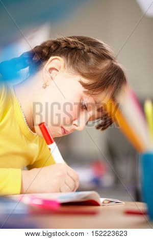 A little schoolgirl absorbed in drawing