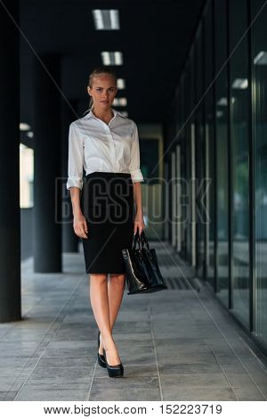 Full length portrait of a young businesswoman standing with black case outdoors