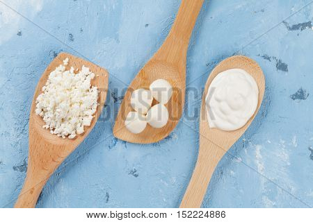 Dairy products spoons over stone table. Sour cream, cheese and curd. Top view