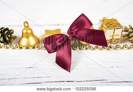 Brilliant gold baubles and cones like christmas decoration. Yellow balls ribbon gift red bow and tinsel isolated on white background.