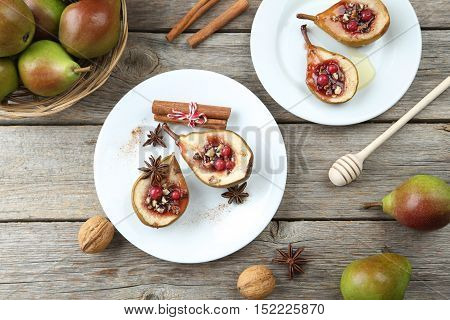 Baked Pears With Honey, Walnuts And Cranberries On Grey Wooden Table