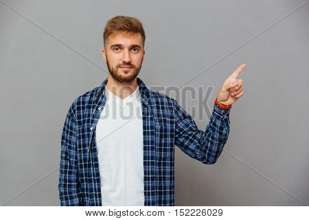 Portrait of a smiling man pointing finger up isolated on a gray background