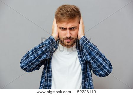 Angry annoyed bearded man covering ears with palms isolated on a gray background