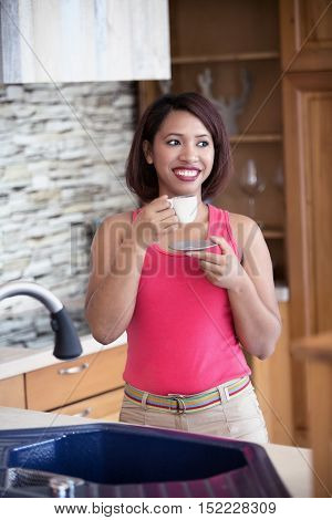 young hispanic woman standing in kitchen and drinking coffee