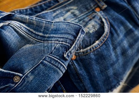 Blue jeans on a brown wooden background