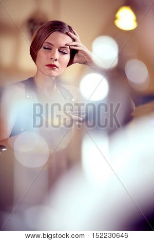 Tired woman with eyes closed holding wineglass