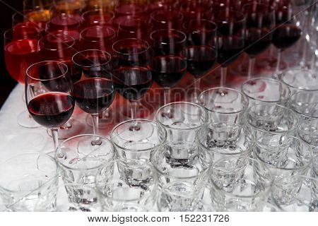 Clean glasses and wineglass with wine closeup on table with white tablecloth
