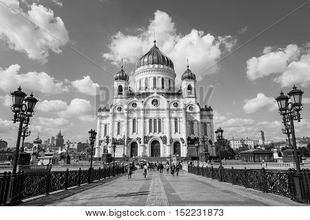 Promenade area in front of Cathedral of Christ the Savior in Moscow Russia. Unidentified motion blurred people walking through the Patriarshiy Bridge at sunny weather. Black and white