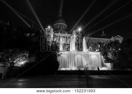 Illuminated National Art museum of Catalonia with fountain in Barcelona Spain at night. Popular landmark dark clear sky. Black and white