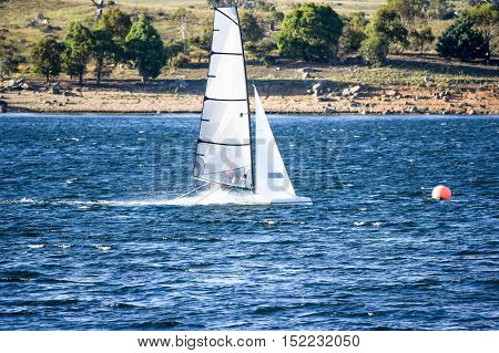 Sail boat approaching a race marker during a local lake race