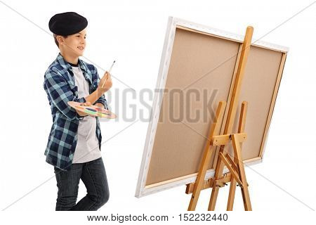 Little boy looking at a canvas and holding a paintbrush and a color palette isolated on white background
