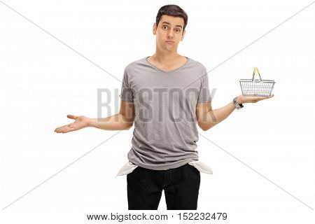 Sad young man showing his empty pockets and  holding a small empty shopping basket isolated on white background