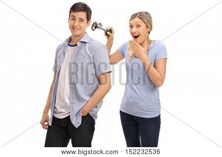 Woman pranking her boyfriend by honking a horn next to his ear isolated on white background
