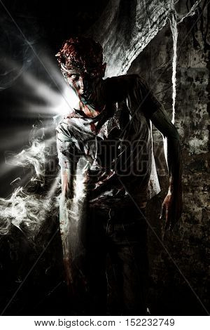 Doomsday. The dead have risen. Frightening bloody zombie in the ruins of the building. Halloween.