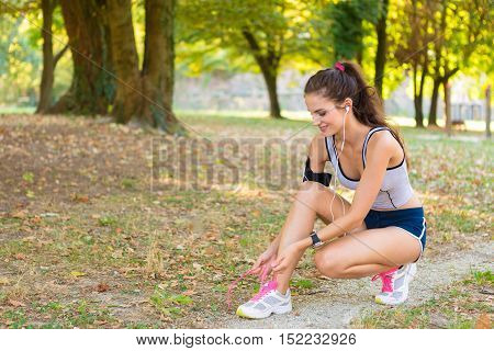 Woman Tying Shoelaces In The Park