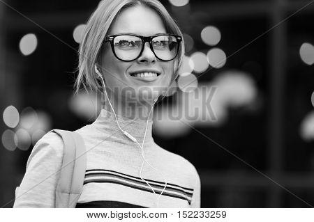 Smiling girl in glasses amid glass door black- white photo