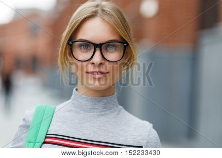 Portrait of smiling student on background of building, blurred background