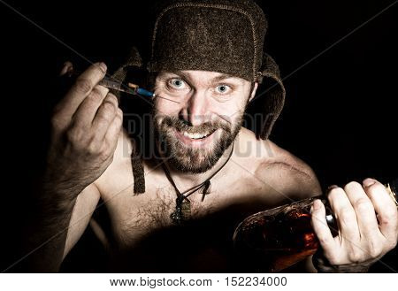 Dark portrait of scary evil sinister bearded man with smirk, offers a variety of drugs, a syringe or a bottle of cognac. strange Russian man with a naked torso and a woolen hat.