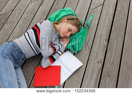 Sleeping girl among open workbooks on wooden floor