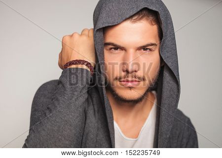 casual man with hoodie on holds hand near head in studio