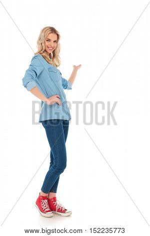full body picture of a smiling young casual woman presenting something on white background