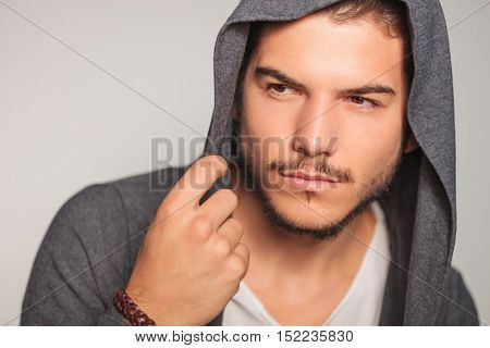 closeup of a young man with hoodie on looking to side in studio