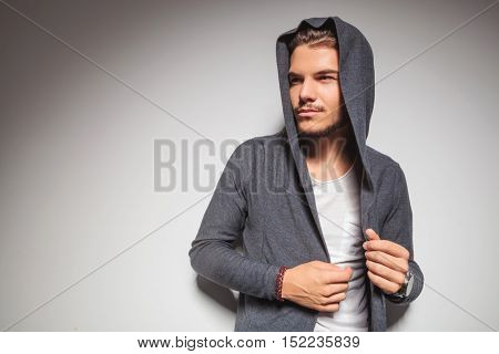 young casual man with hoodie on looking to side on grey studio background